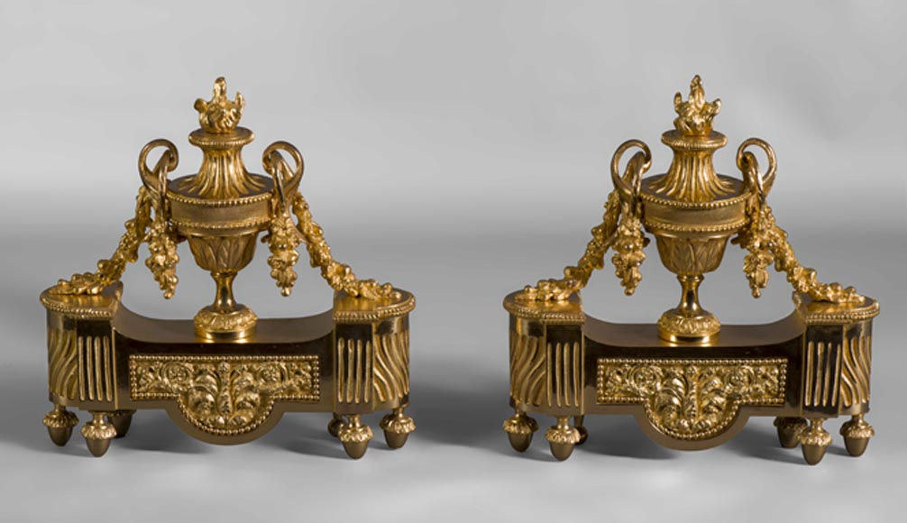 Pair of Louis XVI style andirons in gilt bronze from the 19th century, with vases, garlands of flowers and flames. - Reference 10425
