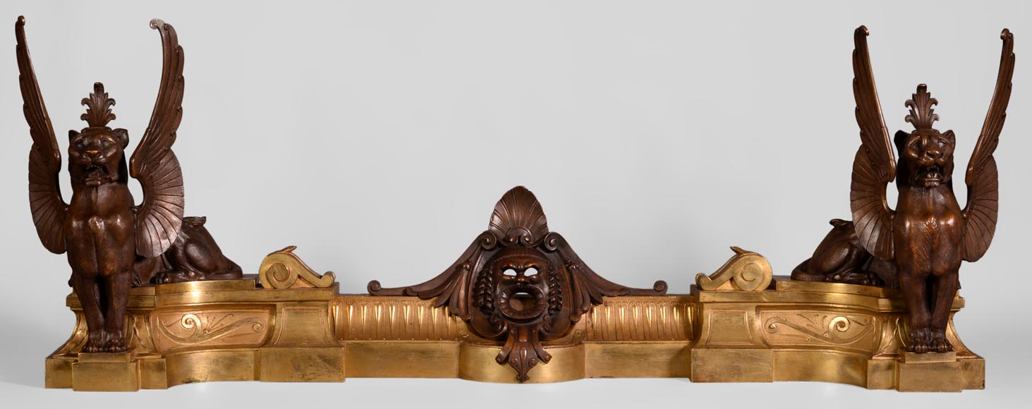 Antique pair of Napoleon III style andirons in gilt bronze and brown patina bronze with winged lions - Reference 10922