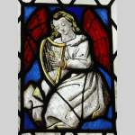 Two stained glasses elements with a harpist and a guitarist angels