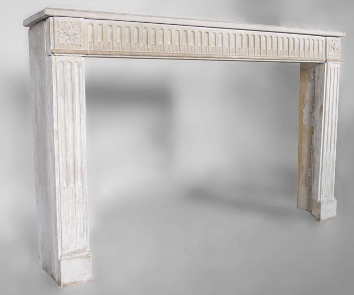 An antique Louis XVI style fireplace made out of stone with flutings-2