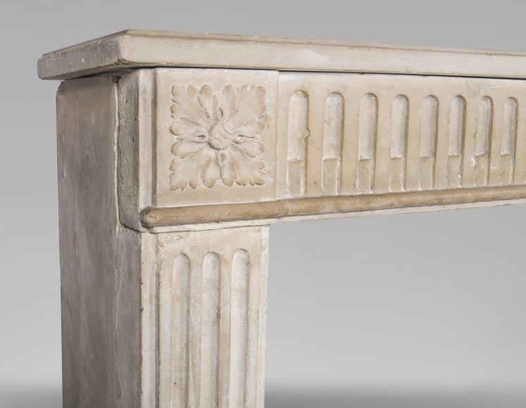 An antique Louis XVI style fireplace made out of stone with flutings-3