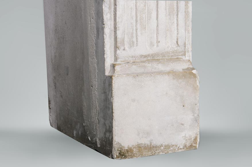 An antique Louis XVI style fireplace made out of stone with flutings-4