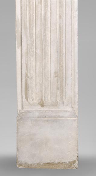An antique Louis XVI style fireplace made out of stone with flutings-7