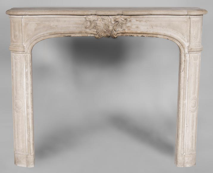 An antique Louis XV style fireplace, made out of stone, with large asymmetrical shell-0