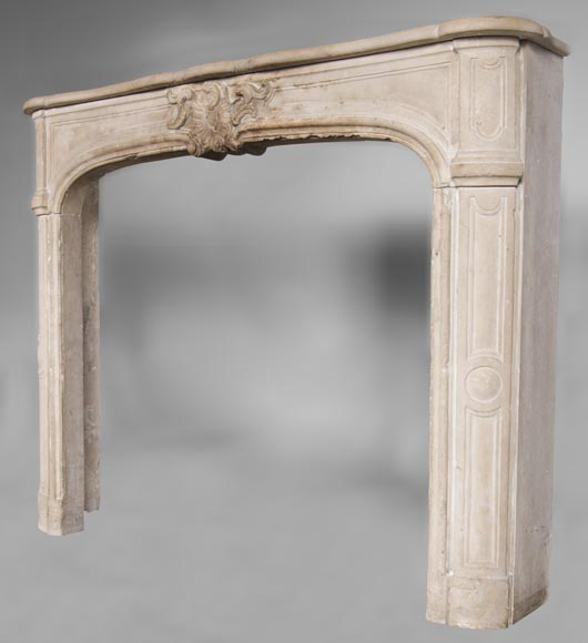 An antique Louis XV style fireplace, made out of stone, with large asymmetrical shell-6
