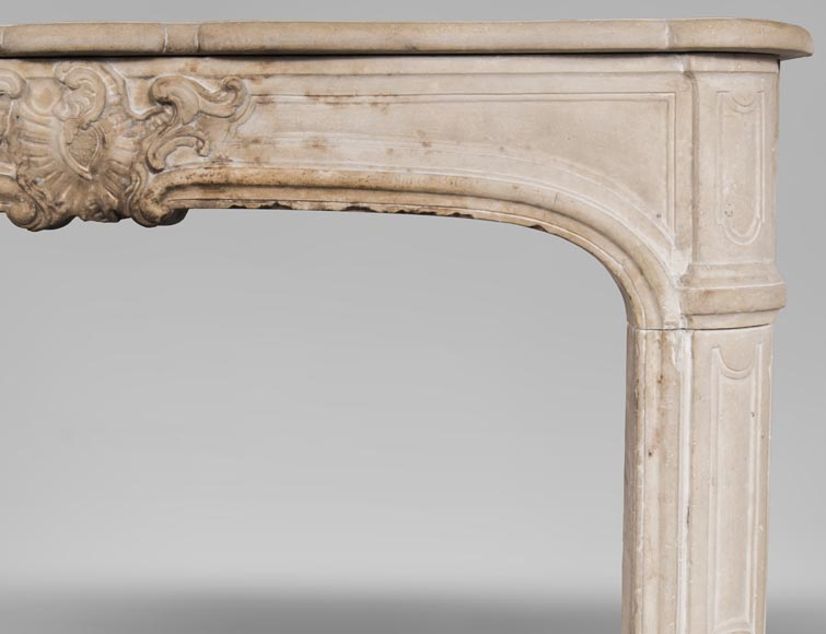 An antique Louis XV style fireplace, made out of stone, with large asymmetrical shell-7