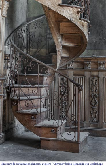 Beautiful spiral staircase with a wrought iron railing decorated with flowers and arabesques-1