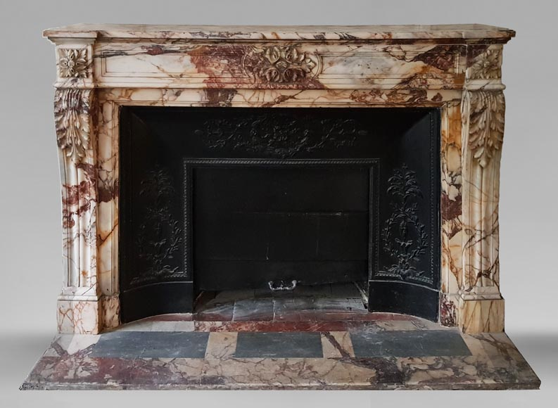 An antique Louis XVI style fireplace, made out of black marble, decorated with a floral cartouche -0