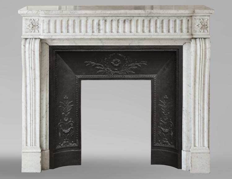 An antique Louis XVI style fireplace with flutes, made out of Carrara marble-0